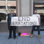 volunteers with sign reading End Deportations