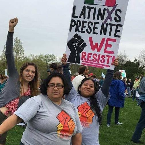 volunteers with sign Latinx presente We Resist